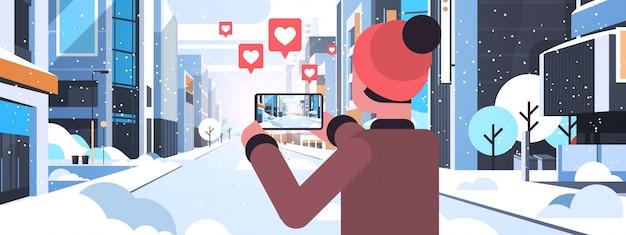 男の旅行者がスマートフォンのカメラで雪に覆われた町の建物を撮影してライブストリーミング