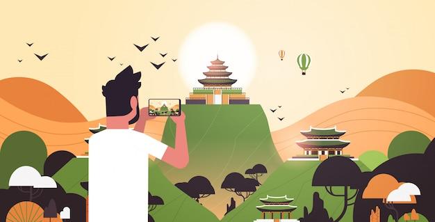 スマートフォンのカメラで伝統的なスタイルで中国の塔を撮影する男性旅行者
