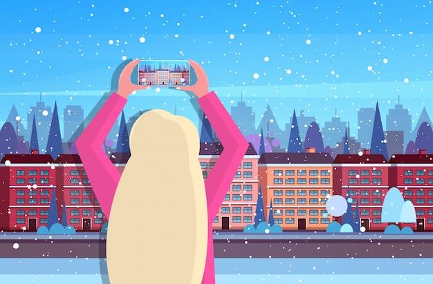 スマートフォンのカメラで町の建物を撮影する女性旅行者旅行ブログコンセプトリアビュー観光観光建築現代冬都市通り水平肖像