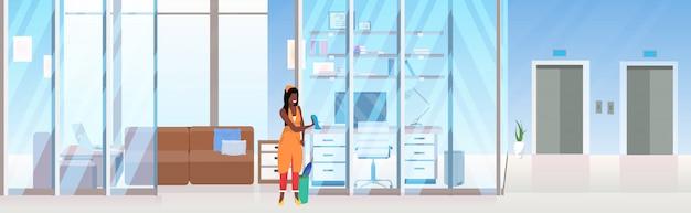 女性クリーナーガラス壁アフリカ系アメリカ人女性用務員がほこりの布クリーニングサービスのコンセプトを使用して創造的な職場のオフィスルームインテリアフラット全長水平