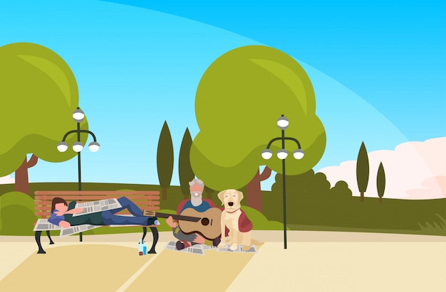 ひげを生やした男のトランプは、木製のベンチ屋外ホームレス失業コンセプト都市公園風景背景水平全長に横たわっているギターを弾いて犬酔って乞食を座っています。
