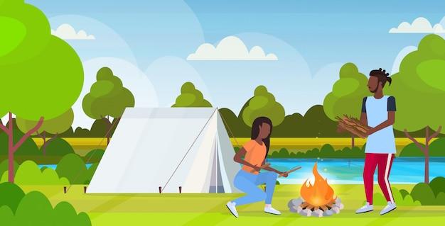 カップルハイキングハイカーテントキャンプ自然風景背景水平全長フラットでたき火ハイキングコンセプトアフリカ系アメリカ人旅行者のための薪を保持している火の男性女性を作る