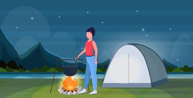 女性ハイカーが食事の女の子を調理するボウラーの沸騰鍋でキャンプファイヤーハイキングコンセプトトラベラーでハイキングテントキャンプの夜の風景の背景全長フラット水平で食べ物を準備します。