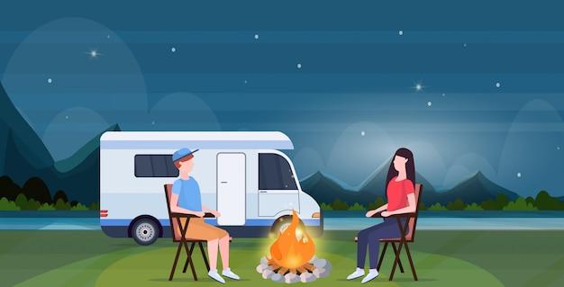 キャンプトレーラートラックキャラバン車の男性女性の支出の時間一緒に夏の休暇の概念の美しい自然の風景の背景全長水平の近くの夜にキャンプファイヤーの周りに座ってカップル