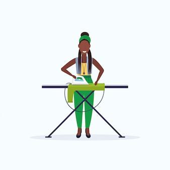 Домохозяйка гладильная одежда афроамериканец женщина держит утюг улыбается девушка делает по дому концепция женщина мультипликационный персонаж полная длина квартира