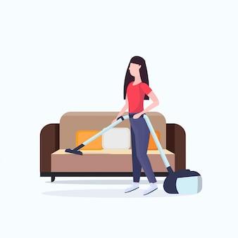 Домохозяйка с помощью пылесоса девушка пылесос кушетка делает по дому уборка концепция уборка полная длина квартира