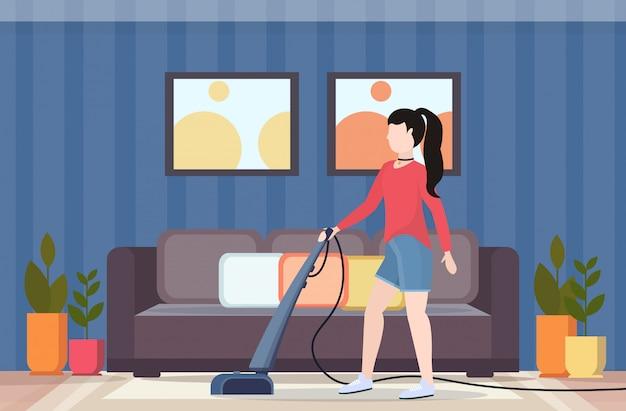 Ключевые слова на русском: женщина с помощью пылесоса домохозяйка делает по дому концепция ухода за полом современный гостиная интерьер плоский полная длина горизонтальный