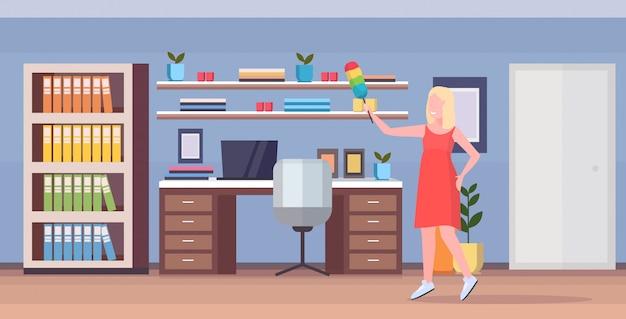 Домохозяйка холдинг пыль щетка женщина уборщик делать по дому полировка деревянная полка уборка концепция уборка современный дом рабочее место интерьер полная длина квартира горизонтальный