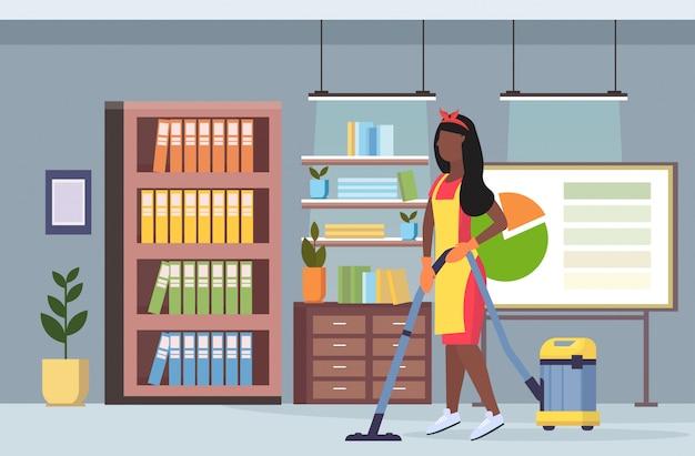 均一な掃除機床クリーニングサービスコンセプトモダンな共同作業センターオフィスインテリアフラット全長水平で掃除機のアフリカ系アメリカ人の女の子を使用している女性