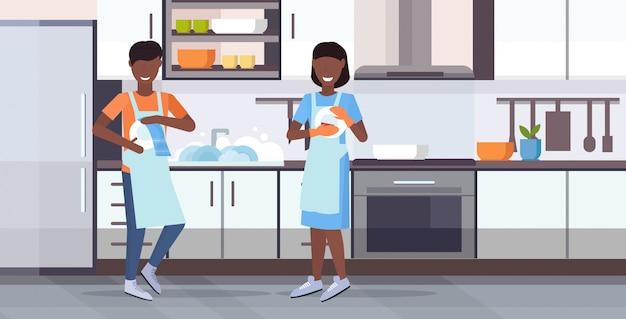 一緒に家事をしているエプロンでタオル食器洗いコンセプトアフリカ系アメリカ人カップルで皿を拭く食器を洗う男女モダンなキッチンインテリア水平フラット全長