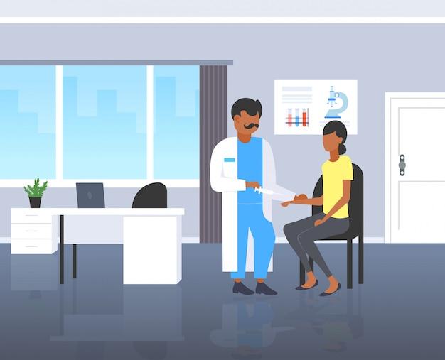 女性患者に注射ワクチンのショットを与える注射器を保持している医者患者患者の予防接種医療医学コンセプトモダンなクリニックルームインテリア全長