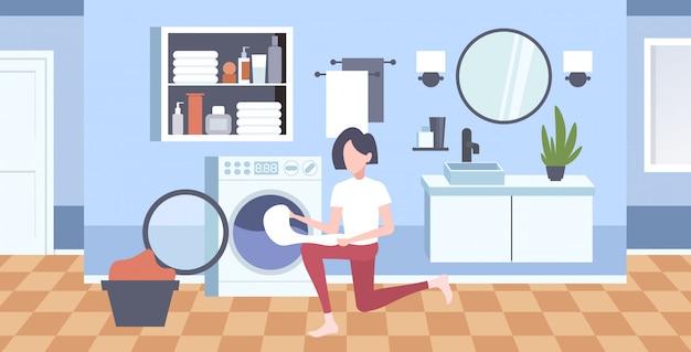 Женщина кладет грязную одежду в стиральную машину домохозяйка делает работу по дому современная прачечная интерьер мультипликационный персонаж полная длина горизонтальный