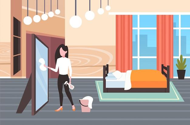 Домохозяйка используя ткань пыли и бутылку с распылителем женщина уборщик вытирая стекло уборка концепция уборка современная спальня интерьер полная длина горизонтальный