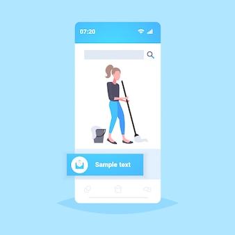 Домохозяйка мытье полов женщина уборщик с использованием швабры уборка по дому концепция смартфона экран мобильного онлайн приложение полная длина