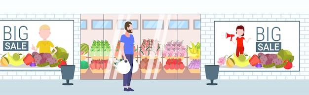 カジュアルな男を保持している購入買い物袋男の前に立っている食料品店スーパーマーケット外装大きな販売ショッピングコンセプト水平全長
