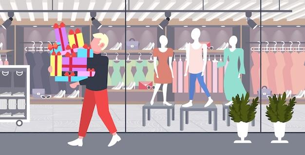 Человек, несущий стопку обернутых подарочных коробок большая сезонная распродажа шоппинг концепция парень держит разноцветные подарки современный бутик модный магазин экстерьер полная длина горизонтальный