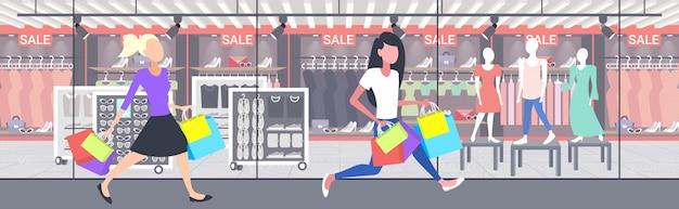 Женщины, несущие сумки, девушки, идущие на открытом воздухе праздник большой концепция продажи современный бутик мода магазин экстерьер полная длина горизонтальный баннер