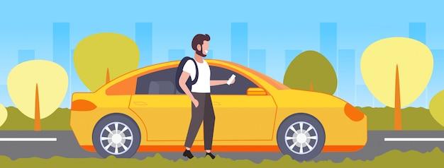 黄色のタクシータクシーレンタルカーシェアリングコンセプト交通サービス都市景観背景全長水平を注文するスマートフォンモバイルアプリ男を使用してカジュアルな男