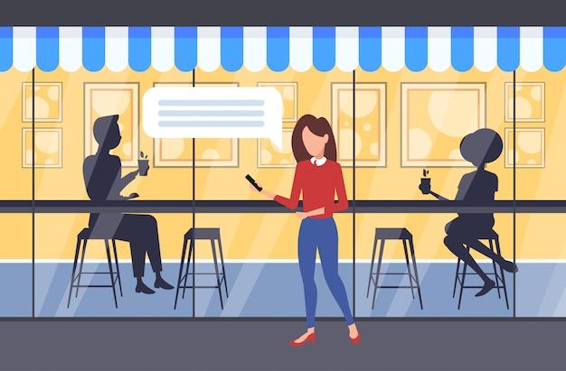 モバイルアプリチャットバブルソーシャルメディア通信音声会話コンセプトカップルシルエットを使用して屋外を歩く女性がテーブルに座ってコーヒーを飲むモダンなストリートカフェ外観全長