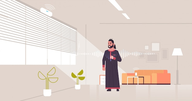 Арабский мужчина с использованием интеллектуального распознавания голоса активированного цифрового помощника