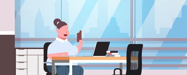 Женщина менеджер, используя ноутбук, едят шоколад, жирная девушка, работник, сидя на рабочем месте, современный офис