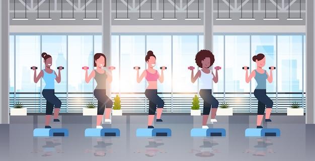 Спортивные женщины, держащие гантели, делающие приседания на ступеньках на платформе, тренировка девушек в тренажерном зале