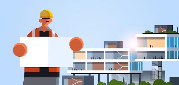空のプラカードボード産業労働者と制服の建物のコンセプトの近代的なオフィスの外観フラットポートレート水平で青写真職人エンジニアを保持している男性のビルダー建築家