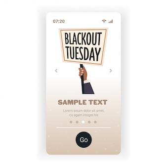 ブラックアウト火曜日のバナーを持っている手黒人種差別に対するキャンペーンの重要なキャンペーン