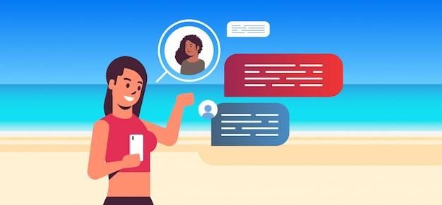 スマートフォンのソーシャルネットワークチャットバブル通信の概念を使用してビキニの女の子