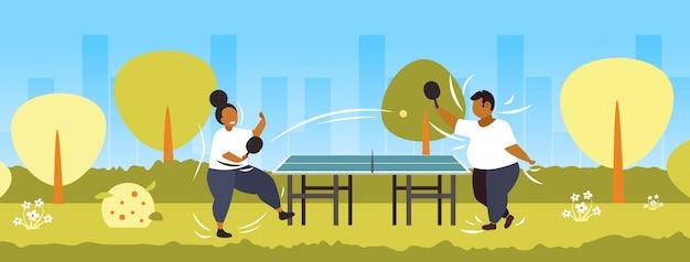 太った肥満のカップルがピンポンテーブルテニスアフリカ系アメリカ人の太りすぎの男性女性楽しんで減量の概念公共公園の風景を再生