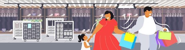 Толстый полные родители с ребенком держа сумку семья весело вместе ходить праздник большой продажа концепция ожирение современный бутик мода магазин интерьер портрет