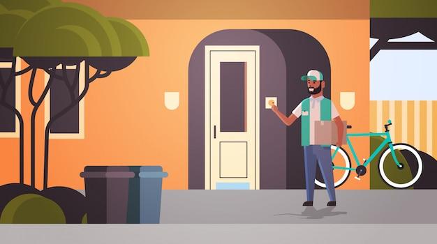 宅配便の男が段ボールの小包リンギングハウスドアベル速達サービスコンセプト水平全長フラットを提供します。