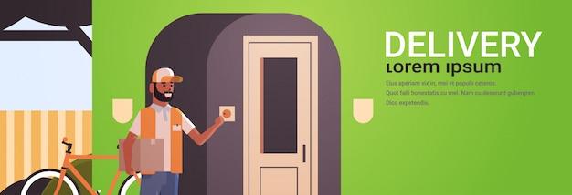 アフリカ系アメリカ人の宅配便の男が段ボールの小包リンギング家玄関の呼び鈴速達サービスコンセプト水平全長フラットコピースペースを提供します。