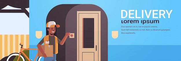 アフリカ系アメリカ人の宅配便の女性が段ボール小包リンギング家玄関呼び鈴速達サービスコンセプト水平全長フラットコピースペースを提供します。