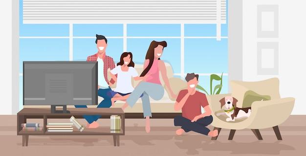 一緒に時間を過ごす犬と一緒にテレビを見て幸せな家族