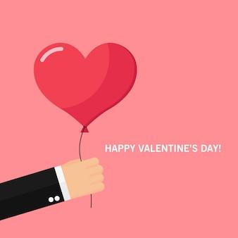 バレンタインデーのために赤い心の風船を持っている男の手