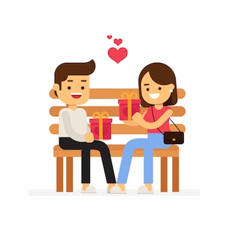 ロマンチックなカップルはベンチに座って、バレンタインデーのためにお互いに贈り物をする