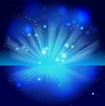 青い夜の背景の上に自由に輝く星