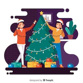 イラストのクリスマスツリーを飾る若者