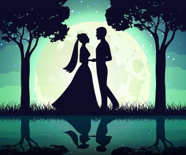 月の背景に新郎新婦のシルエット