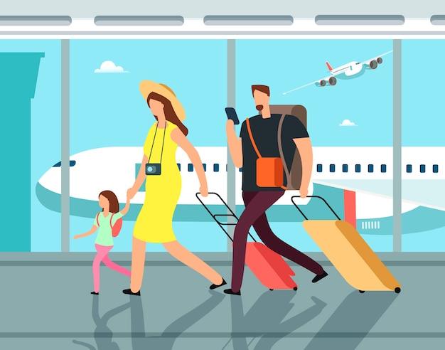 空港ターミナルで荷物を持って旅行中の家族。