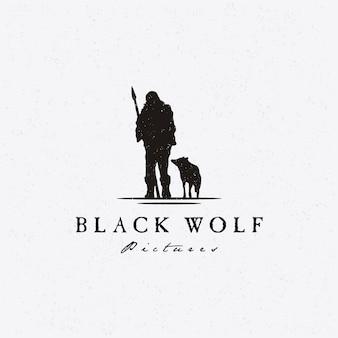素朴なシルエットのオオカミと原始的なハンターのロゴ