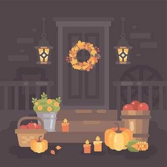 Осеннее крыльцо украшено фонарями, овощами и листьями.