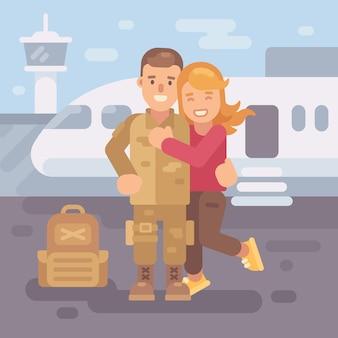 兵士は配備から家に帰る。空港で兵士を抱擁している幸せなガールフレンド