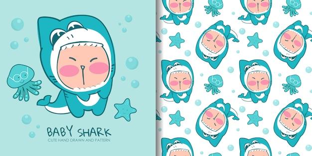 シームレスパターンとサメの衣装で描かれた素敵な子供を手します。