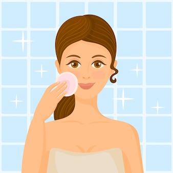 若い女性が綿のパッドで彼女の肌をクリーニング