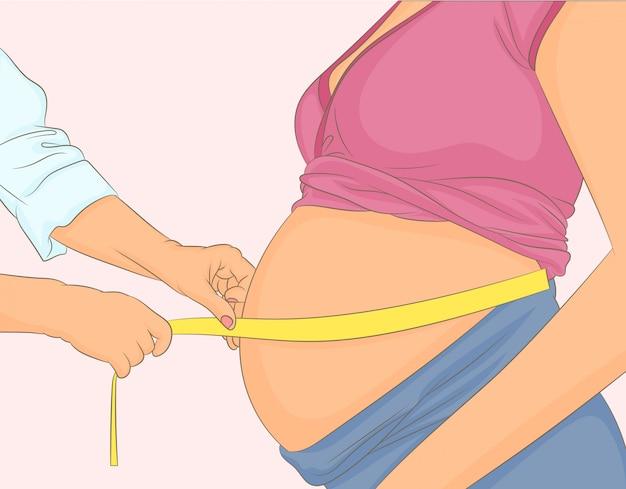 医者は彼女の妊娠中の患者のおなかを測定