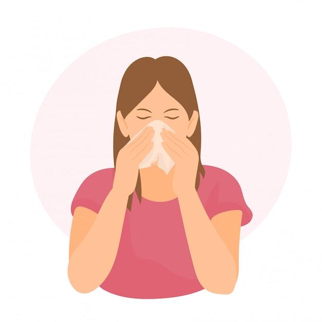Женщина чихает и сморкается в ткани