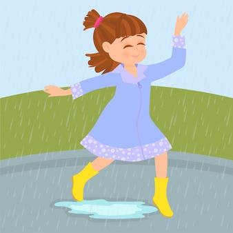 幸せな女の子が雨の中で遊ぶ