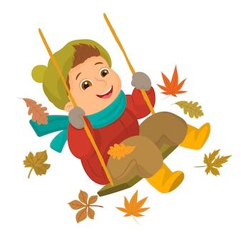Мальчик играет на качелях в осенний сезон